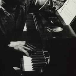 Ulysses Kay playing piano a...