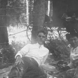 Two Men Lying next to a Wir...