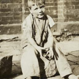 Boy Sitting on Paving Stone