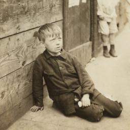Boy Sitting on Sidewalk nea...