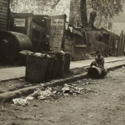 Boy Sitting on Garbage Can