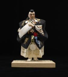 Figurine On Stand  Of Male In Black, Holding Scroll